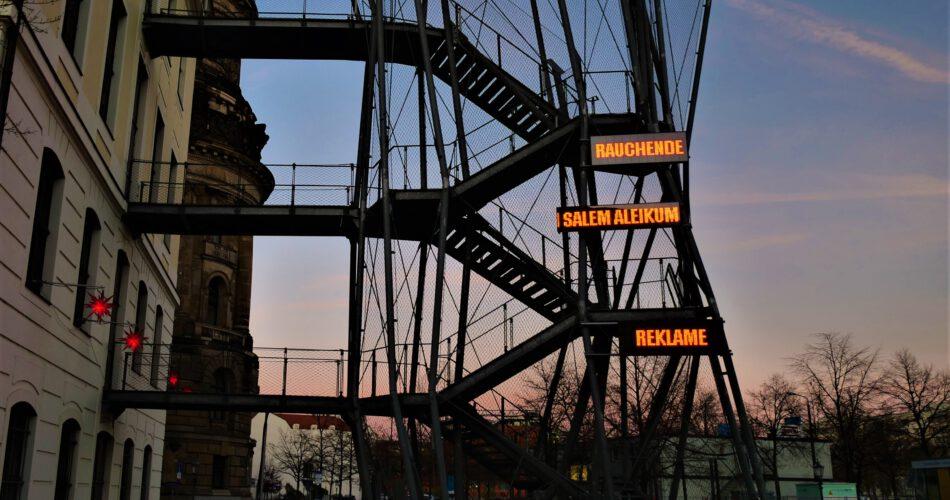 """Eine Installation an der Fluchttreppe des Landhauses zeigt in drei LED-Panels untereinander die Worte """"RAUCHENDE/ SALEM ALEIKUM / REKLAME"""". Die Worte leuchten rot und bewegen sich."""