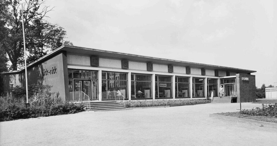 Der Schrägblick auf das pick-nick zeigt einen langgezogenen Pavillonbau mit Schmetterlingsdach und großen Schaufenstern.