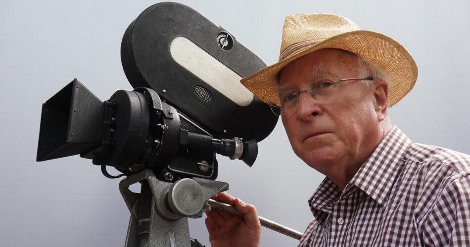 Farbaufnahme von Ernst Hirsch mit Strohut neben einer Kamera der Firma Arriflex.